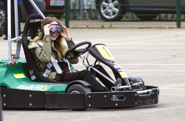 teenager in go kart with vision impairing googles