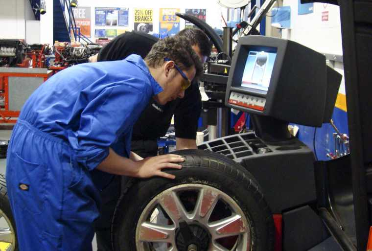 Apprentice using wheel balancing machine
