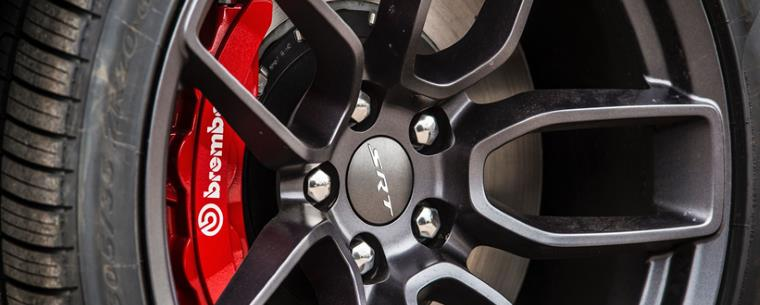 car tyre with the brake rotor on the inside and red brake calipers