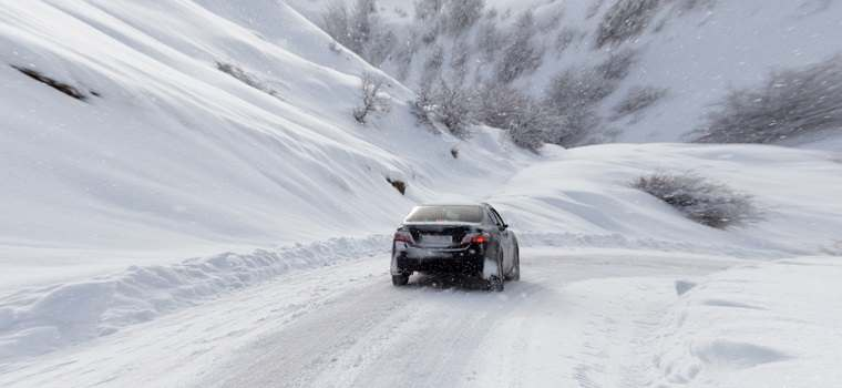 car on mountain road with snow