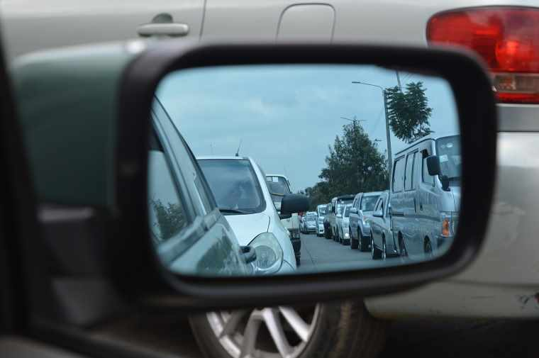 view of traffic in car wing mirror
