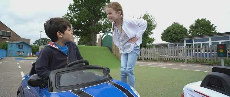 girl telling off boy in motorised car