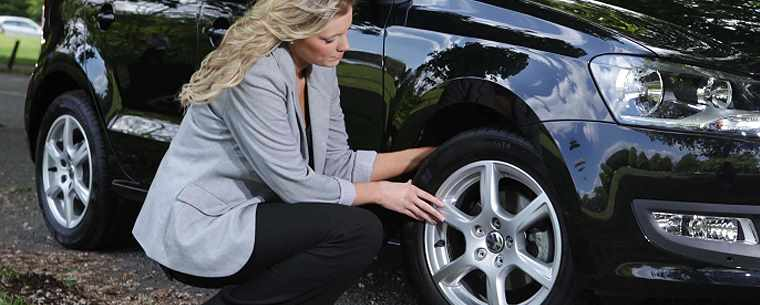 Woman checking car tyres