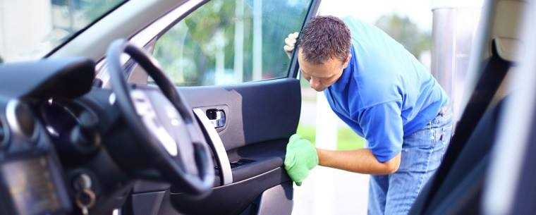 man cleaning inside of car