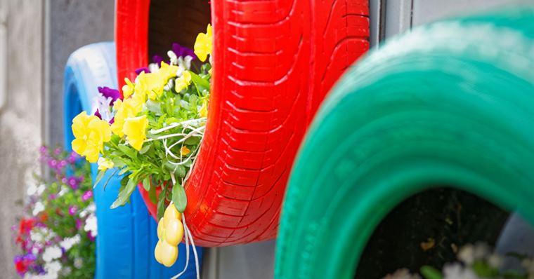 red, green and blue tyres hanging on a wall with plants inside them