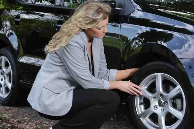 woman checking tyre tread