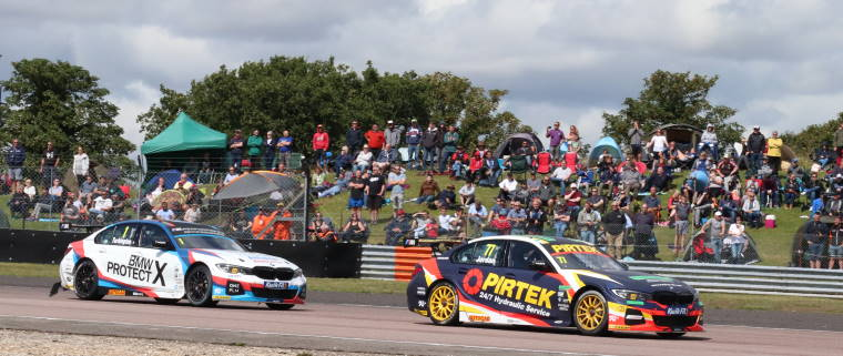 touring cars on racetrack with crowd on hill