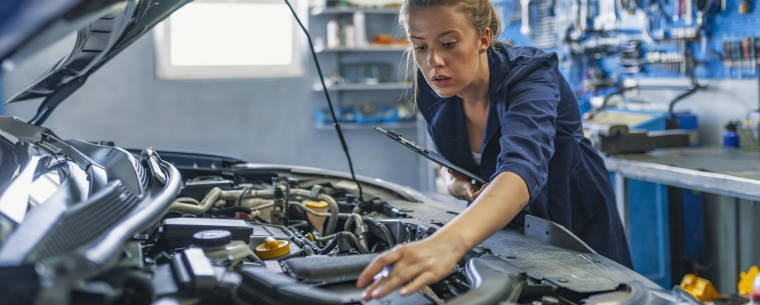 female technician servicing a car at a repair centre