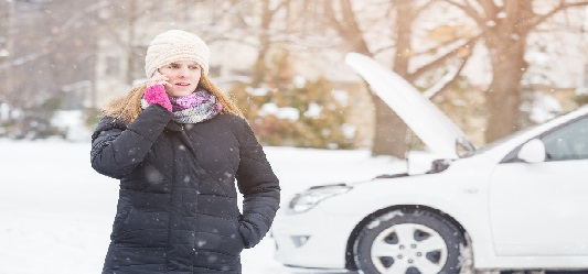 Woman calling breakdown services in the snow
