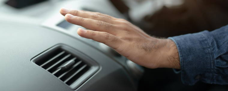 Man Driving While Putting His Hand Over The Air Conditioning Vent