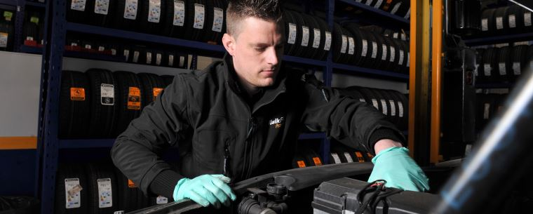 mechanic looking under the hood of a car in a service centre
