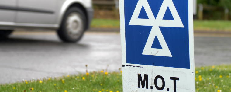 Van Driving Past a Sign at an MOT Test Centre